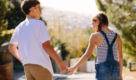 Happy kids in love standing on street and talking. Smiling boy and girl spending time together walking on street outdoors. Boy and girl standing in street and royalty free stock photography