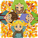 Happy kids lying on colorful autumn leaves in park Royalty Free Stock Images