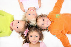 Happy kids lying down on the white. Happy kids lying down on the floor in cross shape Royalty Free Stock Image