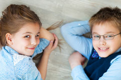 Happy kids are lying together on the floor Royalty Free Stock Photography