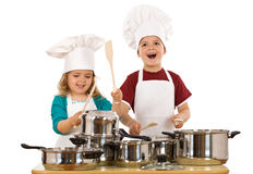 Happy kids making noise. Happy kids dressed as chefs making noise with the cooking pots and wooden spoons - isolated stock image