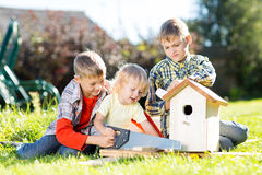 Happy kids making wooden birdhouse by hands. Older child teaches his younger brother. Royalty Free Stock Photo