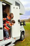 Happy kids near camper (RV) having fun Stock Images