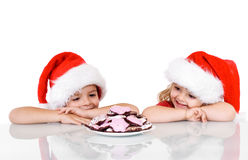 Happy kids near a plate with christmas cookies Stock Photos