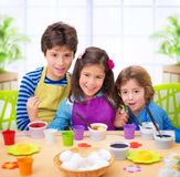 Happy kids paint eggs Stock Photography
