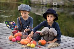 Happy kids paint small Halloween pumpkins. On the river bank Royalty Free Stock Photography