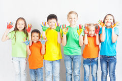 Happy kids with painted hands smiling. And posing at white background. Funny children. International Children's Day. Indian, asian, caucasian - multiracial Royalty Free Stock Photography