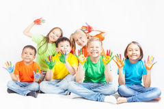 Happy kids with painted hands smiling. And posing at white background. Funny children. International Children's Day. Indian, asian, caucasian - multiracial Royalty Free Stock Images