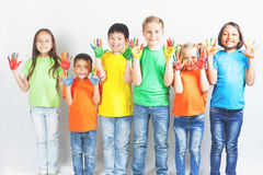 Happy kids with painted hands smiling. And posing at white background. Funny children. International Children's Day. Indian, asian, caucasian - multiracial Stock Photo