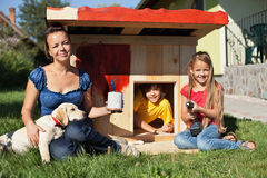 Happy kids painting the doghouse Royalty Free Stock Photography