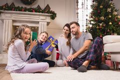 Kids with christmas presents. Happy kids in pajamas holding christmas presents while parents sitting behind at home Stock Photo