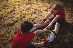 Happy kids performing stretching exercise during obstacle course. In boot camp royalty free stock images