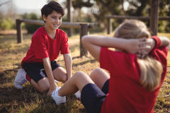 Happy kids performing stretching exercise during obstacle course. In boot camp royalty free stock photo
