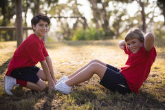 Happy kids performing stretching exercise during obstacle course. In boot camp royalty free stock photography