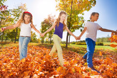 Happy kids play holding hands in the park Stock Photography