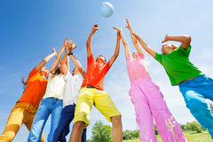 Happy kids playing with ball jumping in air Stock Image