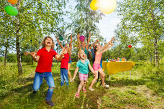 Happy kids playing balloons at summer park. Group of age-diverse kids playing balloons at outdoor party in summer Stock Image