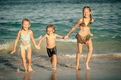 Happy kids playing on beach Stock Photos