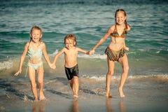 Happy kids playing on beach Stock Photos