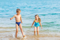 Happy kids playing at the beach shore Stock Photos
