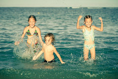 Happy kids playing on beach Stock Images
