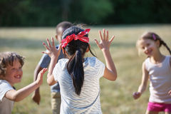 Happy kids playing blind man`s buff. At a birthday party Royalty Free Stock Images