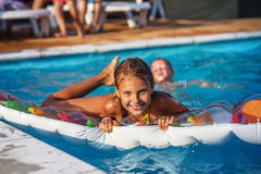 Happy kids playing in blue water of swimming pool. Little children on inflatable mattress in swimming pool. Smiling kids playing and having fun in swimming pool stock image