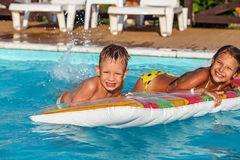 Happy kids playing in blue water of swimming pool. Stock Image
