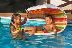 Happy kids playing in blue water of swimming pool. Royalty Free Stock Photo