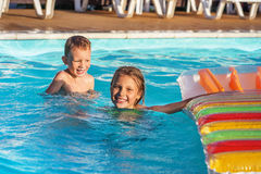 Happy kids playing in blue water of swimming pool. Stock Photos