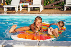 Happy kids playing in blue water of swimming pool. Stock Images