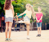 Happy kids playing with chinese jumping rope Stock Photos