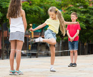 Happy kids playing with chinese jumping rope Royalty Free Stock Images