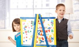 Happy kids playing with drawing board. Portrait of happy kids playing together with drawing board, looking at camera, smiling Stock Photo