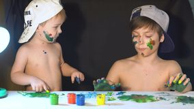 Happy kids playing with finger paints. Two brothers draw fingers on paper. Their hands smeared with paint stock video