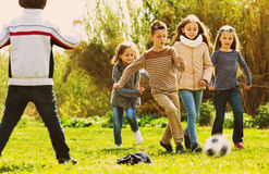 Happy kids playing football outdoors Stock Photos