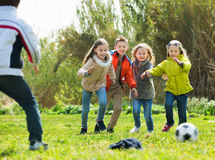 Happy kids playing football outdoors Stock Photography