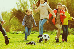Happy kids playing football outdoors Stock Image