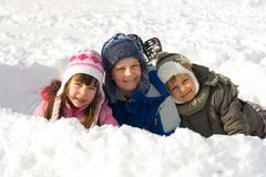 Happy Kids Playing in Fresh Snow. Three happy children, dressed for the cold winter weather, enjoy playing together in fresh, white snow Stock Images