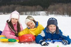 Happy Kids Playing in Fresh Snow. Three happy children on their sleds, enjoying playing in the snow on a cold winter day Royalty Free Stock Image