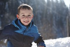 Kids playing with  fresh snow. Happy kids playing in fresh snow at beautiful  sunny winter day Stock Photos