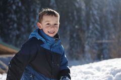 Kids playing with  fresh snow. Happy kids playing in fresh snow at beautiful  sunny winter day Stock Photo