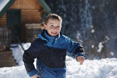 Kids playing with  fresh snow. Happy kids playing in fresh snow at beautiful  sunny winter day Royalty Free Stock Image