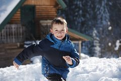 Kids playing with  fresh snow. Happy kids playing in fresh snow at beautiful  sunny winter day Royalty Free Stock Photo