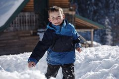 Kids playing with  fresh snow. Happy kids playing in fresh snow at beautiful  sunny winter day Stock Image