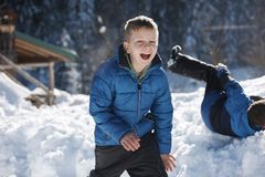 Kids playing with  fresh snow. Happy kids playing in fresh snow at beautiful  sunny winter day Royalty Free Stock Images