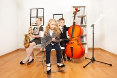Happy kids playing musical instruments together. While sitting inside musical school Royalty Free Stock Images
