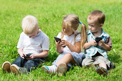 Happy kids playing on smartphones Stock Photos