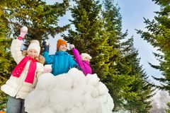 Happy kids playing snowballs game together. Standing behind the snow wall with fir forest on the background during winter day Stock Images