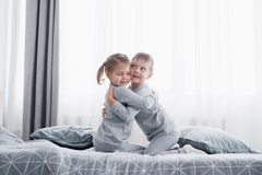 Happy kids playing in white bedroom. Little boy and girl, brother and sister play on the bed wearing pajamas. Nursery. Interior for children. Nightwear and Stock Photos